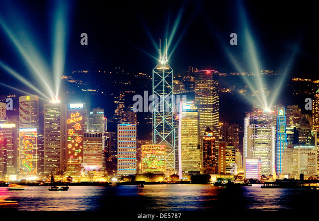 Hong Kong Island China city skyline of Central District at night with laser light show seen across Victoria Harbour - Stock Image