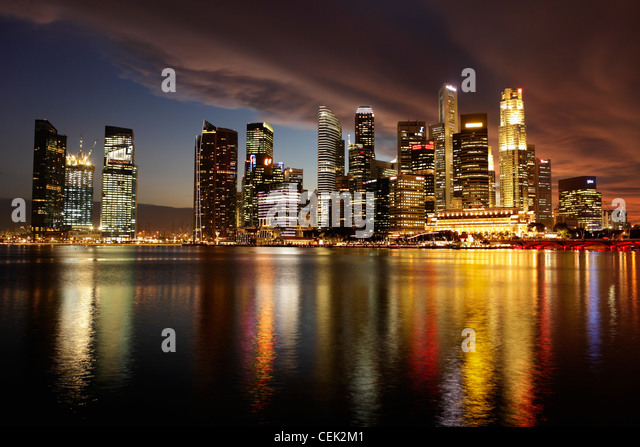 Marina Bay and city skyline reflected in the water at night, Singapore - Stock Image