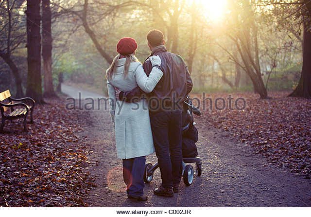 A young couple pushing a stroller in the park, rear view - Stock Image