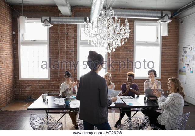 Female designers meeting and clapping in conference room - Stock Image