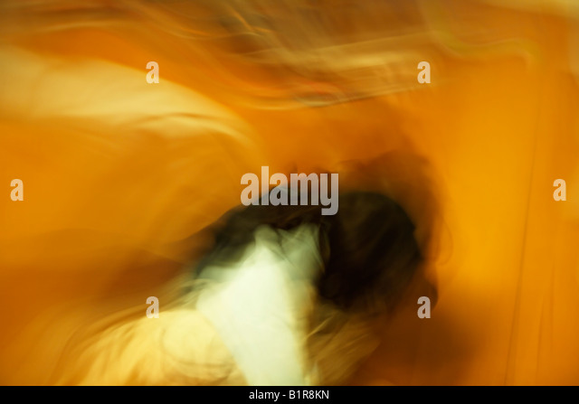 Deliberate long exposure with camera and subject movement creating abstract image Girl aged four runs around her - Stock Image