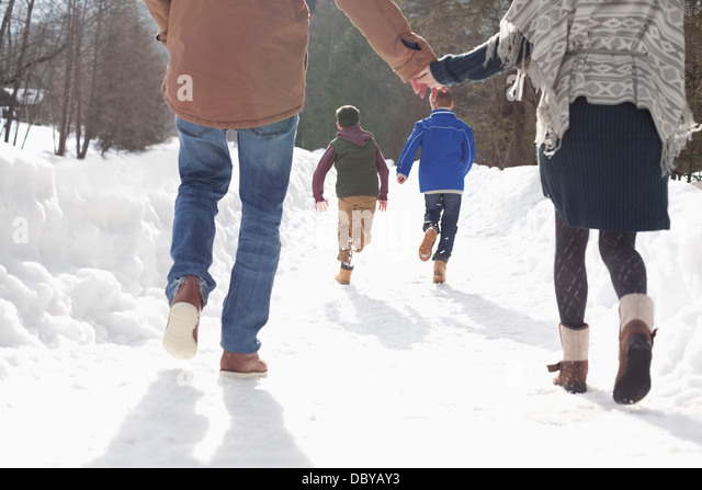 Happy couple holding hands and watching boys run in snowy lane - Stock-Bilder
