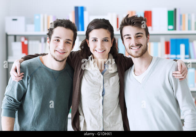 Teenager friends at the library posing together and hugging, youth and friendship concept - Stock Image