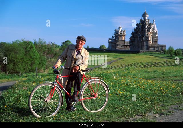 Russia former Soviet Union Karelian Region Kizhi resident bike Transfiguration Cathedral beyond - Stock Image