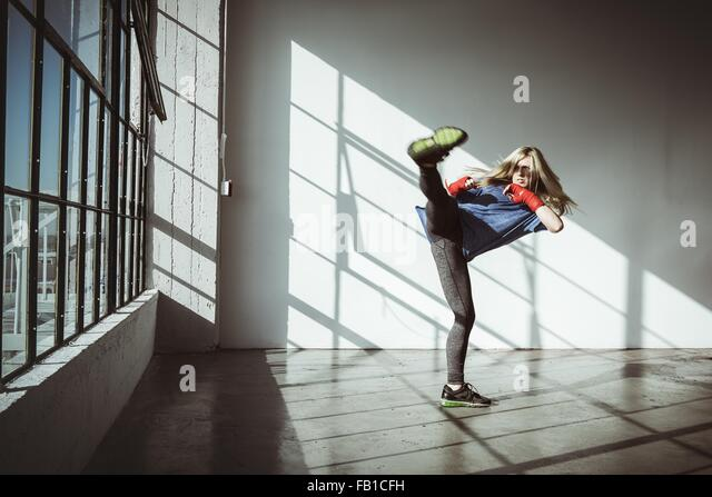 Full length front view of young woman in gym in kickboxing stance looking away - Stock-Bilder