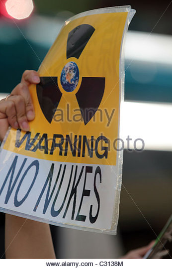 An activist holds up a sign reading 'warning no nukes' during a protest march in Shibuya, Tokyo. - Stock Image