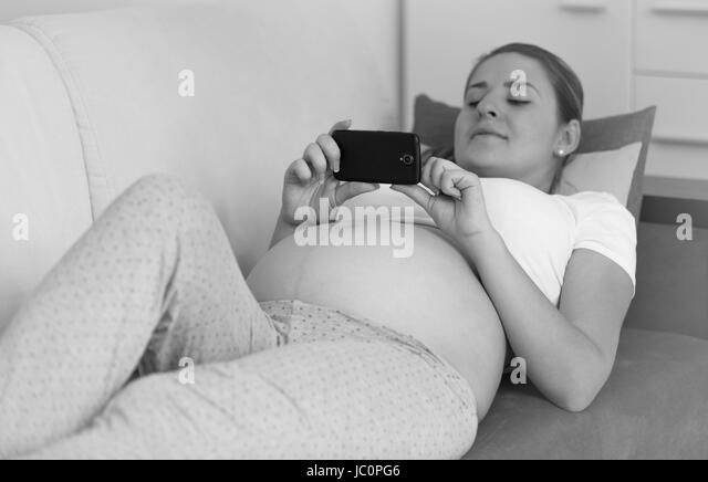 Monochrome photo of pregnant woman typing message on smartphone - Stock Image