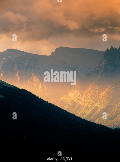 Sun peeking through clouds and shining on mountains of Glacier National Park Montana - Stock-Bilder