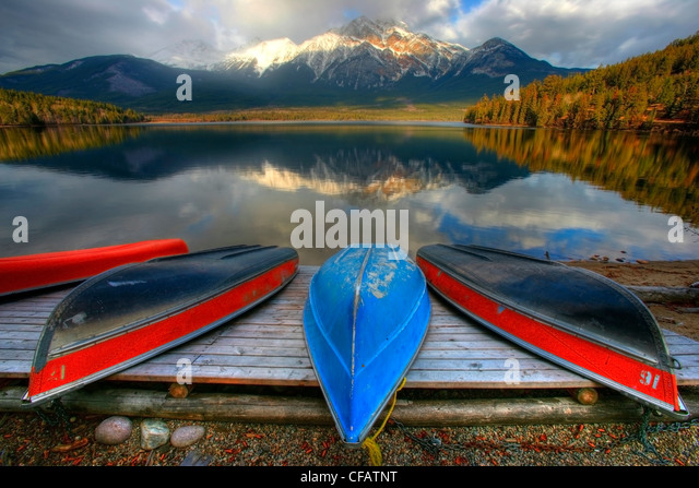 Beached canoes on dock, Pyramid Lake, Jasper National Park, Alberta, Canada - Stock Image