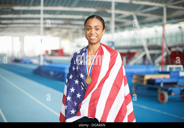 Young female athlete wrapped in US flag with gold medal - Stock Image