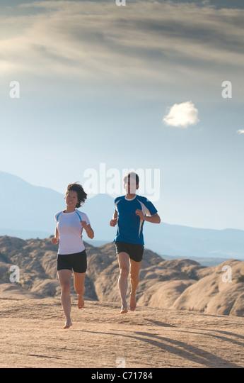 Man and woman  barefoot running in Moab, Utah. - Stock Image