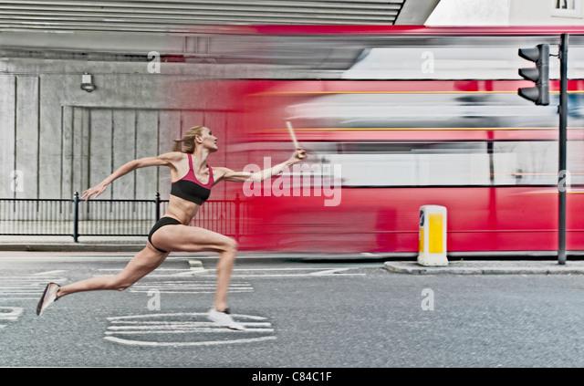 Athlete carrying baton on city street - Stock Image