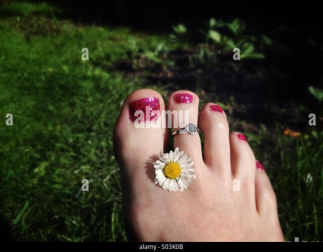 Pretty foot with daisy - Stock Image