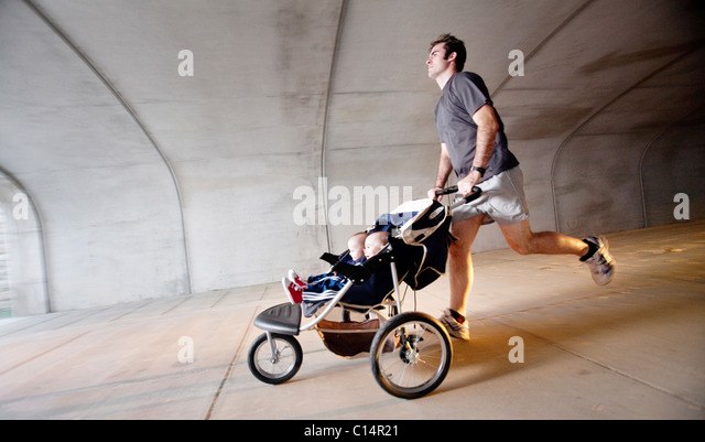 A man runs through a tunnel with his twin sons in a stroller. (Motion Blur) - Stock-Bilder