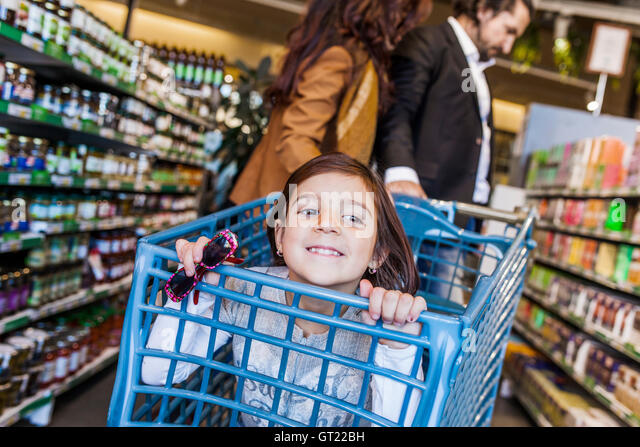Happy girl sitting in cart with parents at supermarket - Stock-Bilder