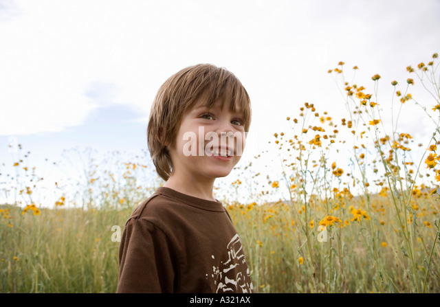 Boy standing in a field - Stock-Bilder