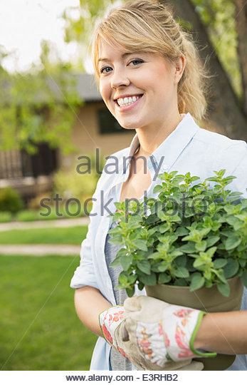 Portrait of smiling woman holding potted plant - Stock Image