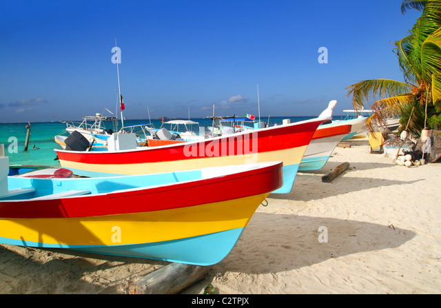colorful tropical boats beached in the sand Isla Mujeres Mexico - Stock Image