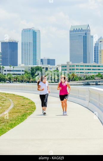 Two women jogging along Bayshore Boulevard with the downtown Tampa, Florida, USA skyline in the background. - Stock Image
