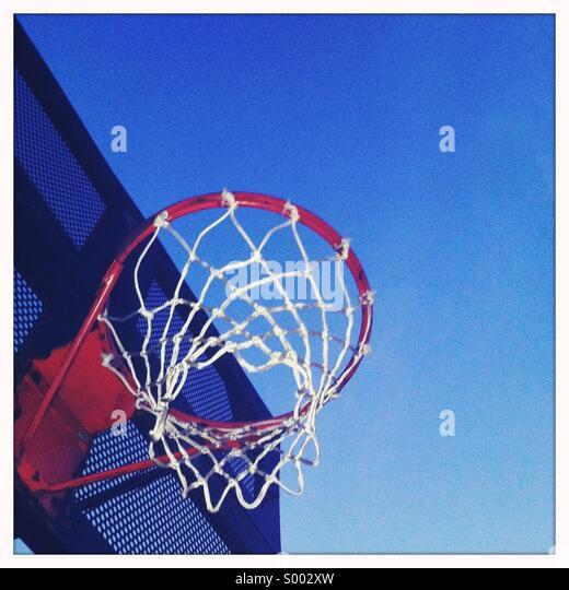 Looking up at a basketball hoop at dusk - Stock Image
