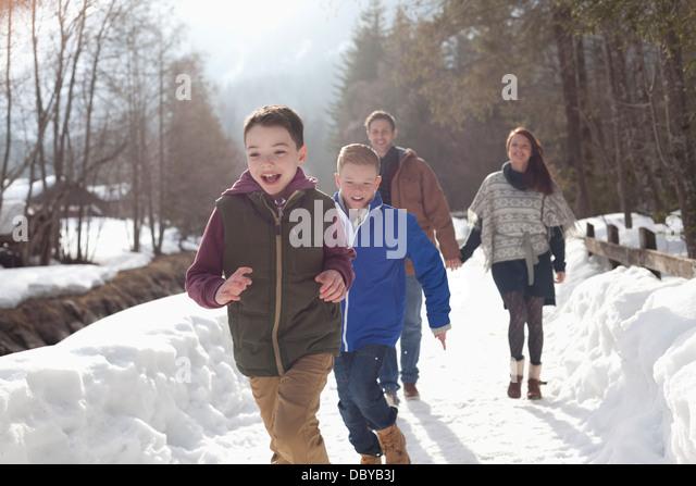 Happy family running in snowy lane - Stock-Bilder