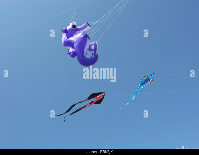 kites flying together in a clear blue sky - Stock Image
