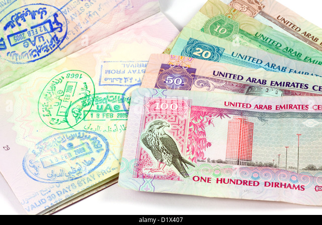 UAE holiday travel money currency and visa stamps in a passport for Dubai and Abu Dhabi - Stock-Bilder