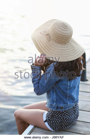 Portrait of a brunette woman in a sun hat by the water - Stock Image