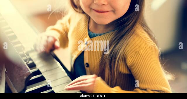 Adorable Cute Girl Playing Piano Concept - Stock Image