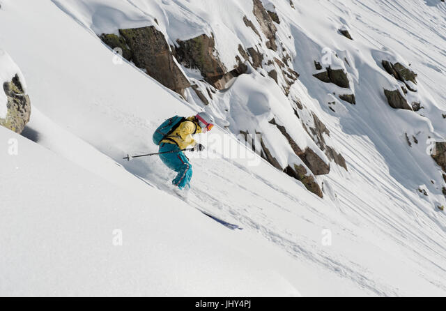 Young woman skiing through fresh powder in the ski area of Disentis 3000 in Switzerland - Stock Image
