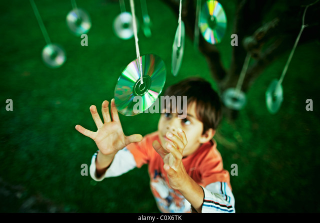 Seven year old boy reaches for discs hung from tree - Stock Image