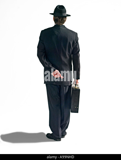 Business man in black suit with black fedora hat and briefcase with fingers crossed behind his back - Stock Image
