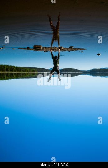 Man doing handstand at McCulloch Lake along the KVR trail, Okanagan Highlands, British Columbia, Canada - Stock Image