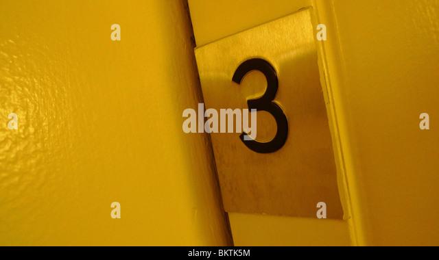 Number three on an elevator door. - Stock Image