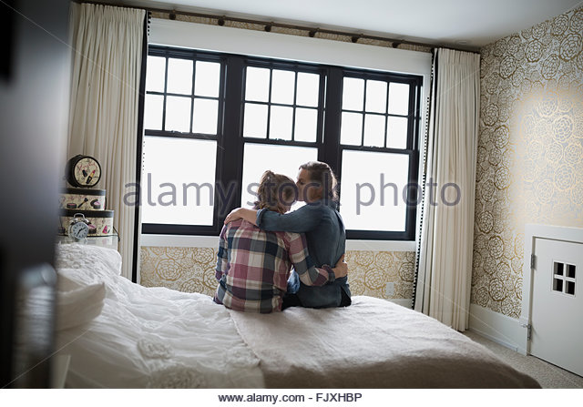 Mother hugging and kissing teenage daughter in bedroom - Stock Image