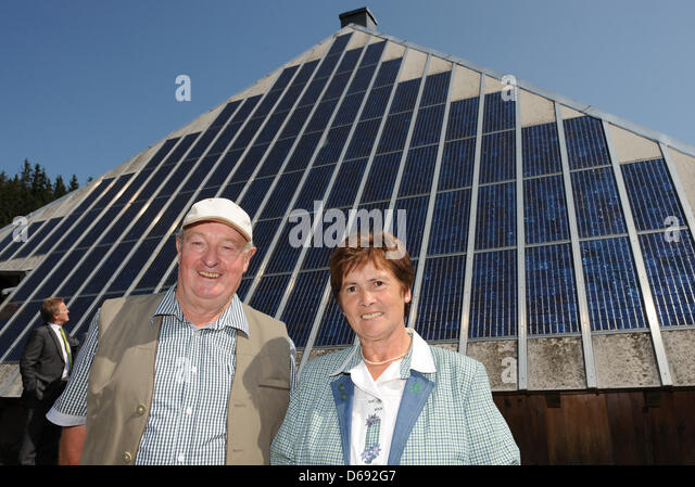 Owners August and Martha Riesterer stand in front of the solar panels on the roof of their inn Rappendecker Huette - Stock Image