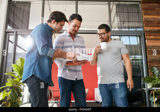 Group of businesspeople discussing paperwork in office. Three young men meeting in office. - Stock Image