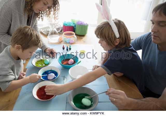 Family in costume rabbit ears dyeing Easter eggs at table - Stock Image