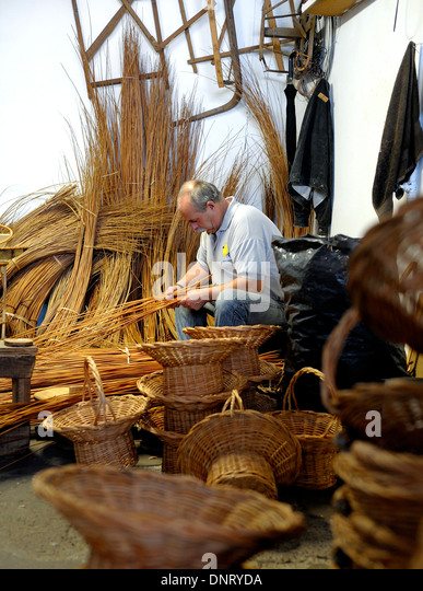 A basket weaver at work in the factory shop in Camacha Madeira Portugal - Stock Image