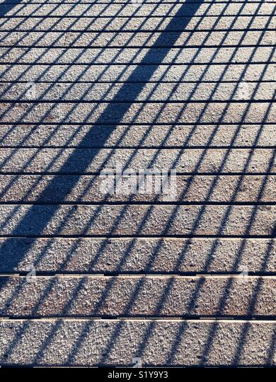Abstract shadows across frost covered wooden deck boards making a geometric pattern - Stock Image