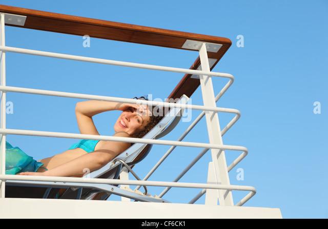 joyful smiling woman wearing swimming suit on deck of cruise ship. - Stock Image