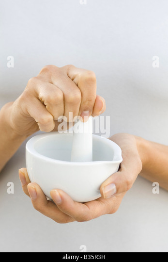 Woman using mortar and pestle, close-up, cropped view - Stock-Bilder