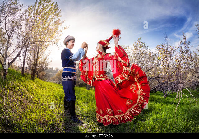 Kazakh woman dancing in red dress with man in Spring apple garden in Almaty, Kazakhstan, Central Asia - Stock Image