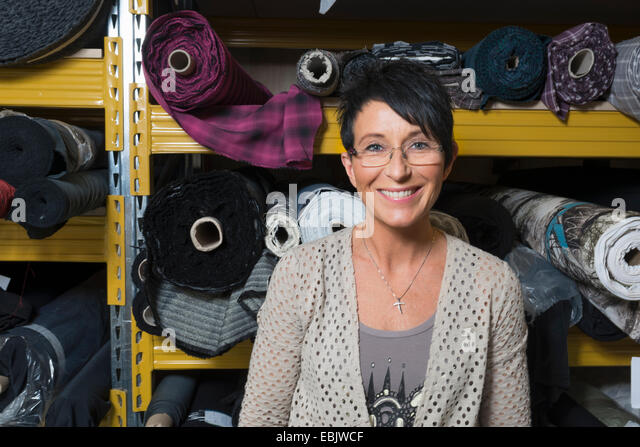 Portrait of mature seamstress in front of rolls of textile in workshop - Stock Image