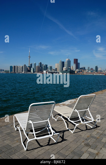 A pair of beach chairs on a promenade overlooking the Toronto skyline and Lake Ontario - Stock Image