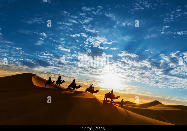 Caravan in the desert during sunrise against a beautiful cloudy sky, Erg Chebbi, Merzouga, Morocco. - Stock Image