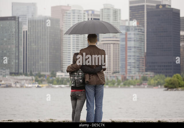 A young couple looking at the city skyline under an umbrella on a rainy day, Vancouver, British Columbia, Canada - Stock Image