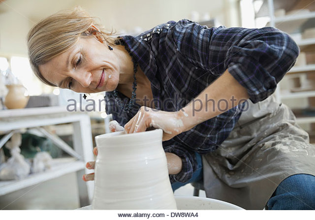 Woman pulling clay on potters wheel - Stock Image
