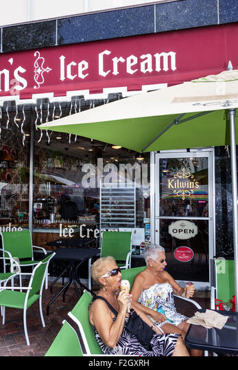 Florida Delray Beach East Atlantic Avenue Kilwin's Ice Cream senior woman friends eating cone active - Stock Image