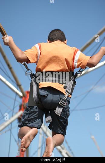 Florida, bungee safety harness, trampoline, gymnastics, jumping, acrobatics, boy, - Stock Image